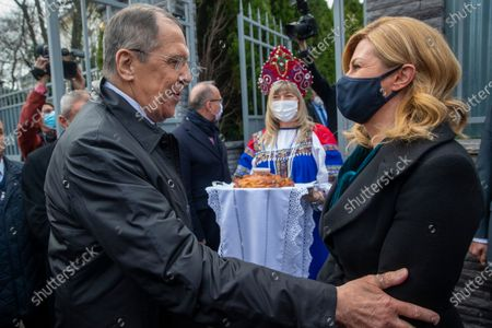 Russian Foreign Minister Sergey Lavrov, left, greets former Croatian President Kolinda Grabar-Kitarovic, in front of the Russian embassy in Zagreb, Croatia, . Lavrov is on a one-day visit to Croatia