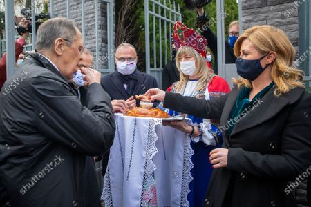 Russian Foreign Minister Sergey Lavrov, left, and former Croatian President Kolinda Grabar-Kitarovic, right, have traditional Russian bread in front of the Russian embassy in Zagreb, Croatia, . Lavrov is on a one-day visit to Croatia