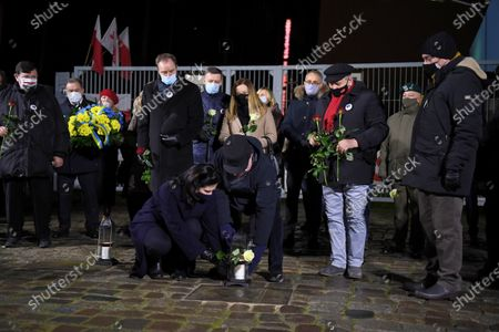 Former Polish President and leader of the Independent Polish Trade Union Solidarity, Nobel Peace Prize laureate Lech Walesa (C-R) and Mayor of Gdansk Aleksandra Dulkiewicz (C-L) attend the ceremony of lighting candles and laying flowers at the Gate No 2 of the Gdansk Shipyard in Gdansk, northern Poland, 16 December 2020. Ceremonies are held to observances marking the 50th anniversary of the tragic anti-communist protests of December 1970.