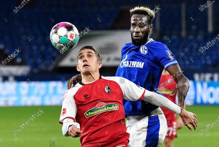 Stock Photo of Freiburg's Nils Petersen, left, and Schalke's Salif Sane challenge for the ball during the German Bundesliga soccer match between FC Schalke 04 and SC Freiburg at the Arena in Gelsenkirchen, Germany