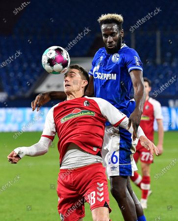 Freiburg's Nils Petersen, left, and Schalke's Salif Sane challenge for the ball during the German Bundesliga soccer match between FC Schalke 04 and SC Freiburg at the Arena in Gelsenkirchen, Germany