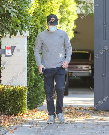 Matt Damon keeps his head low in a baseball cap while visiting Ben Affleck
