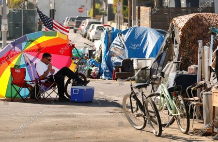 Stock Picture of 45-year-old Richard Thompson seeks the shade of his umbrella as he is camped out with several others in a Venice parking lot across the street from one of 20 homeless shelters that have been established by Mayor Garcetti but homeless continue to sleep on the streets near the shelters even as the Mayor has promised to maintain clean streets around them. Downtown on Friday, Nov. 13, 2020 in Los Angeles, CA. (Al Seib / Los Angeles Times