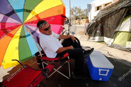 45-year-old Richard Thompson seeks the shade of his umbrella as he is camped out with several others in a Venice parking lot across the street from one of 20 homeless shelters that have been established by Mayor Garcetti but homeless continue to sleep on the streets near the shelters even as the Mayor has promised to maintain clean streets around them. Downtown on Friday, Nov. 13, 2020 in Los Angeles, CA. (Al Seib / Los Angeles Times
