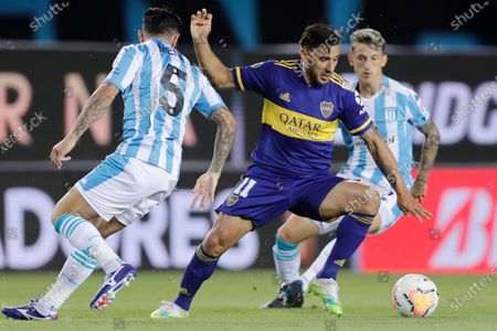 Eduardo Salvio of Argentina's Boca Juniors dribbles past Eugenio Mena of Argentina's Racing Club during a Copa Libertadores quarterfinal first leg soccer match at the Presidente Peron stadium in Buenos Aires, Argentina
