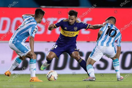 Eduardo Salvio of Argentina's Boca Juniors, center battles for the ball with Matias Rojas and Alexis Soto, both of Argentina's Racing Club, during a Copa Libertadores quarterfinal first leg soccer match at the Presidente Peron stadium in Buenos Aires, Argentina
