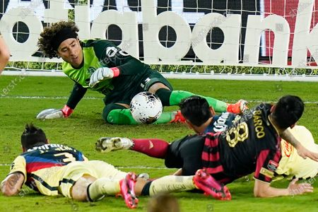 Club America goalkeeper Guillermo Ochoa, center, blocks a shot by Atlanta United midfielder Ezequiel Barco (8) during the first half of a CONCACAF Champions League soccer match, in Orlando, Fla