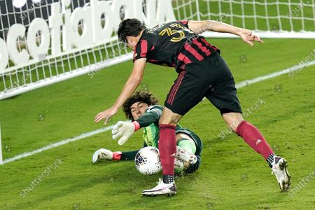 Club America goalkeeper Guillermo Ochoa, lower left, blocks a shot on goal by Atlanta United forward Erick Torres (31) during the second half of a CONCACAF Champions League soccer match, in Orlando, Fla