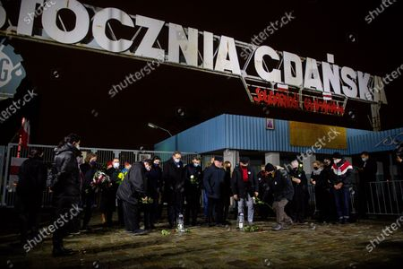 Stock Picture of Mayor of Gdansk Aleksandra Dulkiewicz (L) Marshal of Pomeranian Voivodeship Mieczyslaw Struk (C) and former President of Poland Lech Walesa (R) are seen under the historic Gate no. 2 of Gdansk Shipyard during the celebrations of anniversary of December 1970 in Gdansk. On December 14-22, 1970, there were riots and strikes due to the rise in retail food prices by the authorities. During these events 40 people were killed and more than 1,100 were injured. The largest workers strikes took place in Gdansk, Gdynia, Szczecin and Elblag. They were suppressed by the army and the militia.