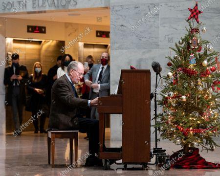 U.S. Senator Lamar Alexander (R-TN) playing Christmas songs on a piano in the atrium of the Hart Senate Office Building.