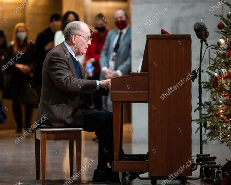 Stock Picture of U.S. Senator Lamar Alexander (R-TN) playing Christmas songs on a piano in the atrium of the Hart Senate Office Building.