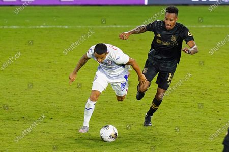 Cruz Azul midfielder Yoshimar Yotun (19) moves the ball past Los Angeles FC midfielder Mark-Anthony Kaye, right, during the second half of a CONCACAF Champions League soccer match, in Orlando, Fla
