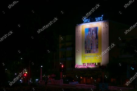 A portrait of King Maha Vajiralongkorn, and Queen Suthida, on the royal hotel at Sanam Luang during the night in Bangkok.