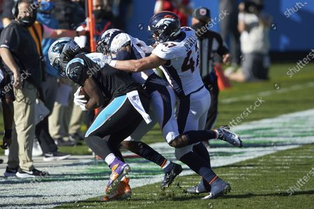 Carolina Panthers tight end Ian Thomas (80) is forced out of bounds by Denver Broncos cornerback Michael Ojemudia (23) and linebacker Josey Jewell (47) during an NFL football game, in Charlotte, N.C