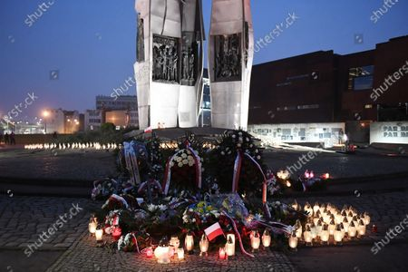 Polish President Andrzej Duda (C-R) lights candle at the Monument to the fallen Shipyard Workers 1970, in Gdansk, north Poland, 17 December 2020.