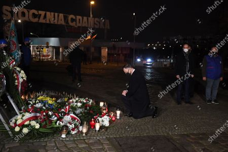 Polish President Andrzej Duda (3R) lights candle at the Monument to the fallen Shipyard Workers 1970, in Gdansk, north Poland, 17 December 2020.