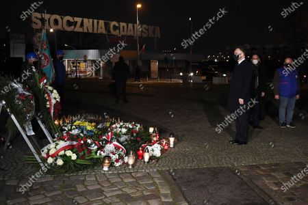 Polish President Andrzej Duda (2L) lights candle at the Monument to the fallen Shipyard Workers 1970, in Gdansk, north Poland, 17 December 2020.
