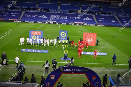 Players and officials take part in a minute of applause in memory of former Lyon manager Gerard Houllier prior to the French league 1 match