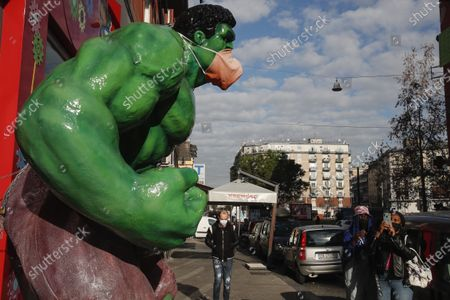 A figure of Marvel Comics character Hulk wearing a protective face mask stands in front of a toy shop