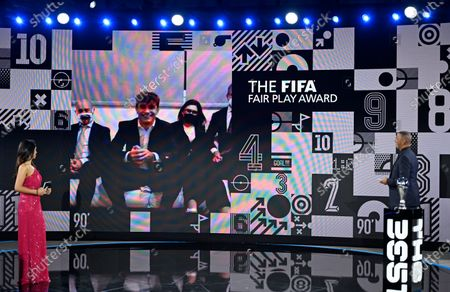 Mattia Agnese on screen after being given the Fair Play award by hosts Reshmin Chowdhury, right, and former Dutch soccer player Ruud Gullit at the start of the Best FIFA Football Awards Ceremony in Zurich, Switzerland