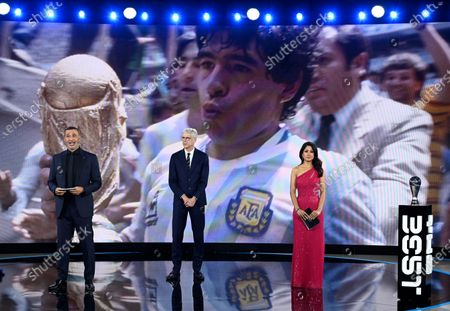 Hosts Reshmin Chowdhury, right, former Dutch soccer player Ruud Gullit, left, and former Arsenal coach Arsene Wenger during a homage to the recently deceased Argentine soccer legend Diego Maradona during the Best FIFA Football Awards Ceremony in Zurich, Switzerland