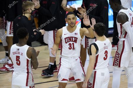 Guard Marvin Coleman (31) high fives UNLV guard David Jenkins Jr. (5) and UNLV guard Caleb Grill (3) during team introductions before the start of the first half of an NCAA college basketball game against North Carolina in the Maui Invitational tournament, in Asheville, N.C