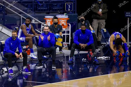 Duke head coach Mike Krzyzewski claps as players and coaches sit distanced on the team bench during an NCAA college basketball game against Notre Dame, in South Bend, Ind. Duke won 75-65