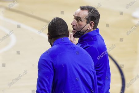 Duke head coach Mike Krzyzewski pulls his mask down to talked to an assistant coach during an NCAA college basketball game against Notre Dame, in South Bend, Ind. Duke won 75-65
