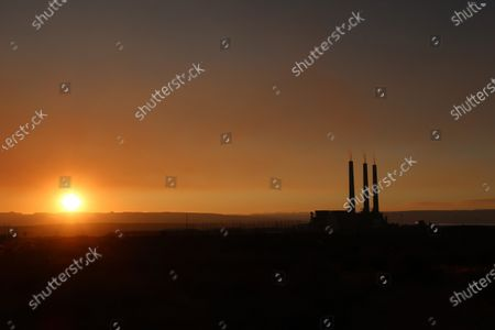 Stock Picture of The sun setting behind the coal-fired Navajo Generating Station near Page, Ariz. The three towering concrete stacks are the most visual reminder of a coal-fired power plant that operated for decades in far northern Arizona. On, they are scheduled to come down. The 775-foot structures loomed over the Navajo Generating Station, which closed last year
