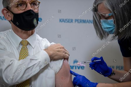 Stock Photo of Kaiser Permanente registered nurse Corie Robinson administers the Pfizer-BioNTech vaccine for COVID-19 to District of Columbia Fire and EMS medical director Dr. Robert Holman during a vaccine event at Kaiser Permanente Capitol Hill Medical Center in Washington