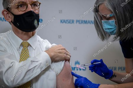 Kaiser Permanente registered nurse Corie Robinson administers the Pfizer-BioNTech vaccine for COVID-19 to District of Columbia Fire and EMS medical director Dr. Robert Holman during a vaccine event at Kaiser Permanente Capitol Hill Medical Center in Washington