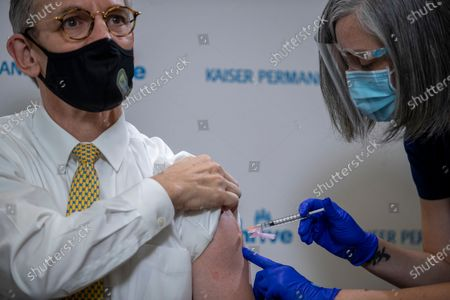 Kaiser Permanente registered nurse Corie Robinson administers the Pfizer-BioNTech vaccine for COVID-19 to DC Fire and EMS medical director Dr. Robert Holman during a vaccine event during a vaccine event at Kaiser Permanente Capitol Hill Medical Center in Washington