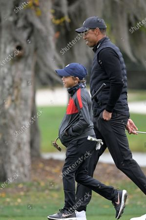 Tiger Woods, right, and his son Charlie walk on the 11th hole during a pro-am round of the PNC Championship golf tournament, in Orlando, Fla