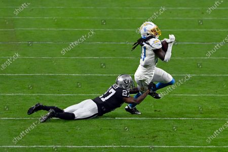 Los Angeles Chargers wide receiver Mike Williams (81) runs with the ball under pressure from Las Vegas Raiders cornerback Trayvon Mullen (27) during an NFL football game, in Las Vegas