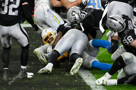 Los Angeles Chargers running back Kalen Ballage (31) scores a touchdown under Las Vegas Raiders middle linebacker Raekwon McMillan during the second half of an NFL football game, in Las Vegas