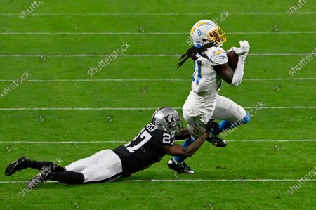 Stock Photo of Las Vegas Raiders cornerback Trayvon Mullen (27) tackles Los Angeles Chargers wide receiver Mike Williams (81) during the first half of an NFL football game, in Las Vegas