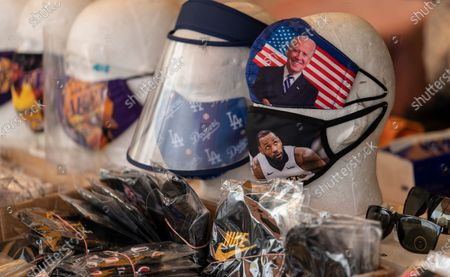 Face masks with the likeness of President-elect Joe Biden, and Los Angeles Lakers LeBron James are sold in the Chinatown district of Los Angeles . California health authorities reported more coronavirus deaths and new confirmed cases as the crisis over care of the sick deepened