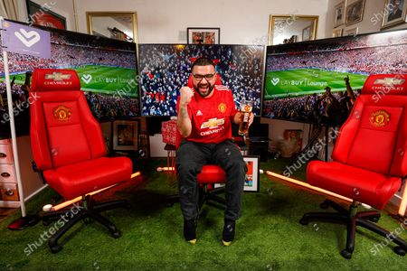 Stock Image of HOME GOAL: Christmas came early for Manchester United superfan, Shaun Leahy, 31, yesterday, after he was surprised by footballing legend Andy Cole, who partnered with club partner, Laybuy to transform the key worker's Coventry home into the grounds of Old Trafford - complete with Christmas dinner, cheering crowds and his own personal dug-out. With this Christmas marking the first time in the club's 142-year history than fans will be unable to attend festive matches, Shaun and his family were treated to the club's first ever at-home Christmas hospitality experience to watch the Red Devil's winning match against Sheffield United on Thursday Night