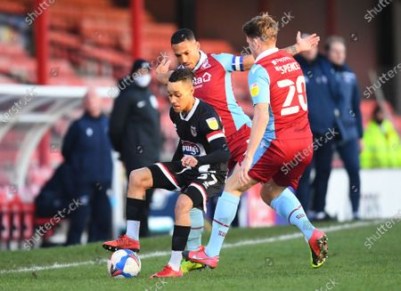 Kyle Bennett of Grimsby Town takes on Jordan Clarke and Lewis Spence of Scunthorpe United