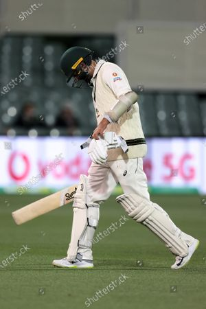 Nathan Lyon of Australia walks off after being caught out by Virat Kohli Captain of India