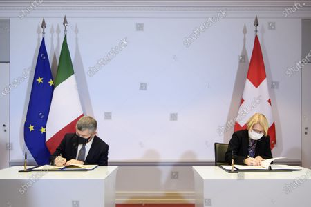Ivan Scalfarotto (L), Italian Undersecretary for Foreign Affairs, and Swiss State Secretary Livia Leu (R) sign a bilateral state agreement in the field of radiometric controls at the borders, at Bellevue Palace, in Bern, Switzerland, 18 December 2020.