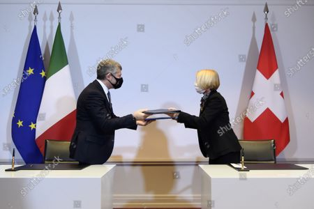 Ivan Scalfarotto (L), Italian Undersecretary for Foreign Affairs, and Swiss State Secretary Livia Leu (R) exchange a bilateral state agreement in the field of radiometric controls at the borders, at Bellevue Palace, in Bern, Switzerland, 18 December 2020.