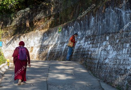 An exile Tibetan Buddhist nun walks past another Tibetan touching his head in reverence on the outer wall of the residence of Tibetan spiritual leader the Dalai Lama in Dharmsala, India