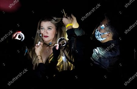 Masked crew members style host Kelly Clarkson during a commercial break at the Billboard Music Awards, at the Dolby Theatre in Los Angeles