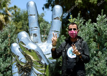 """Musician Ringo Starr poses in front of his """"Peace and Love"""" public sculpture on his 80th birthday, in Beverly Hills, Calif"""