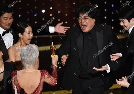 "Bong Joon Ho, right, reacts as he is presented with the award for best picture for ""Parasite"" from presenter Jane Fonda at the Oscars, at the Dolby Theatre in Los Angeles. Looking on from left are Song Kang-Ho and Kwak Sin Ae"