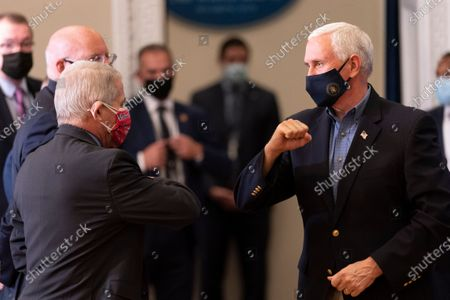 Vice President Mike Pence greets Dr. Anthony Fauci, left, director of the National Institute for Allergy and Infectious Diseases, as he leaves after getting a Pfizer-BioNTech COVID-19 vaccine shot at the Eisenhower Executive Office Building on the White House complex, in Washington
