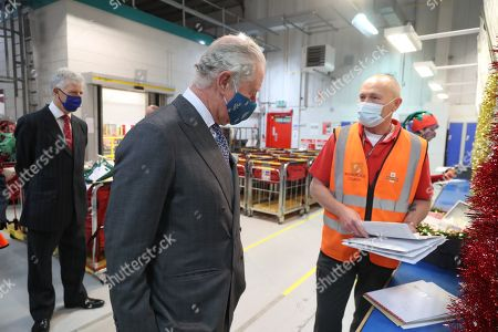 Prince Charles, wearing a mask because of the coronavirus pandemic, meets with Royal Mail employee Mark Gardiner (R) as he visits Royal Mail's Delivery Office. Prince Charles visited the Royal Mail in Cirencester to recognise the vital public services that the country's postal workers provide, especially during the coronavirus pandemic and in the run-up to Christmas