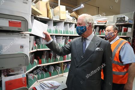 Prince Charles (L), wearing a mask because of the coronavirus pandemic, helps to sort the mail with Royal Mail employee Mark Messer (R) on a visit to Royal Mail's Delivery Office. Prince Charles visited the Royal Mail in Cirencester to recognise the vital public services that the country's postal workers provide, especially during the coronavirus pandemic and in the run-up to Christmas