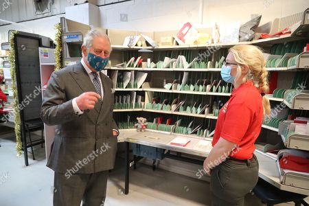 Prince Charles (L), wearing a mask because of the coronavirus pandemic, meetings Royal Mail employee Sarah Burton (R) on a visit to Royal Mail's Delivery Office. Prince Charles visited the Royal Mail in Cirencester to recognise the vital public services that the country's postal workers provide, especially during the coronavirus pandemic and in the run-up to Christmas